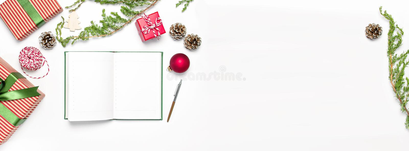 Open notebook with blank pages, gift boxes, fir branches on white background flat lay top view. Christmas planning concept Holiday. Decorations 2019 Goals. New stock photo