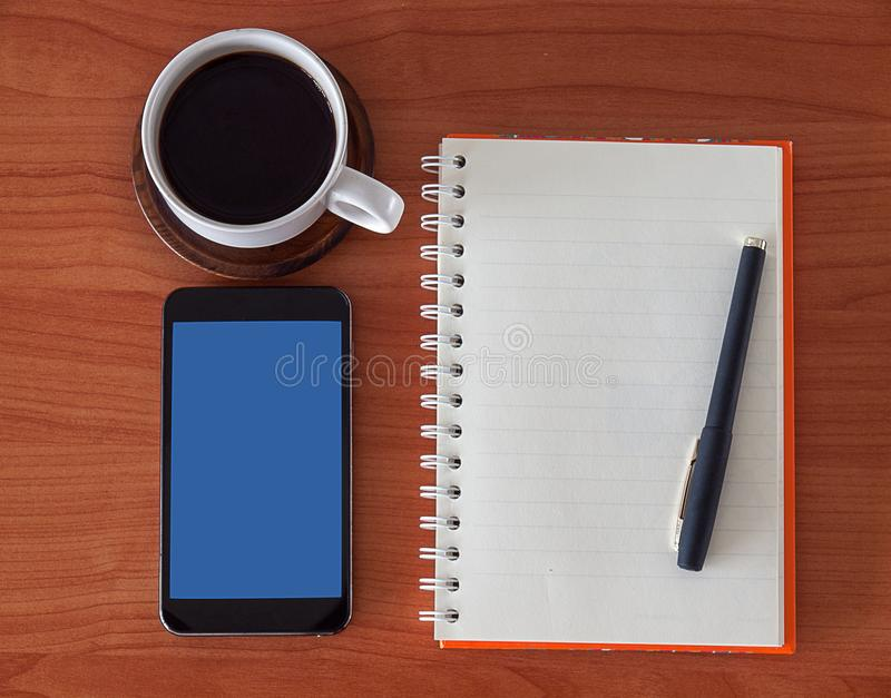 Open notebook with blank pages, mobile phone and coffee cup. royalty free stock image