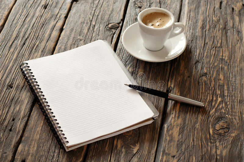 Open notebook with blank pages and pen with coffee espresso. Open notebook with blank pages and pen with cup of coffee espresso on the dark wooden surface, top royalty free stock photos