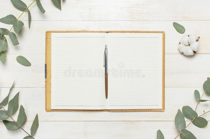 Open notebook with blank pages, pen, eucalyptus twig and cotton flowers on white wooden background top view flat lay. Fashion. Female blogger working desk royalty free stock photography