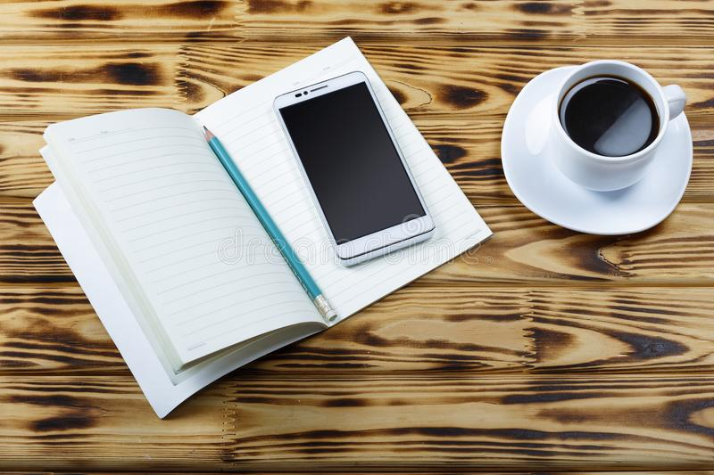 Open notebook, blank pages, pencil, white smartphone, cup of black coffee on office table or on table in a cafe. Concept: work in stock photos