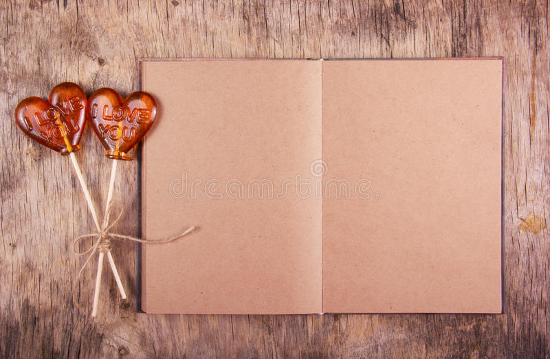 Open notebook with blank pages and two lollipop in the shape of a heart. royalty free stock photography