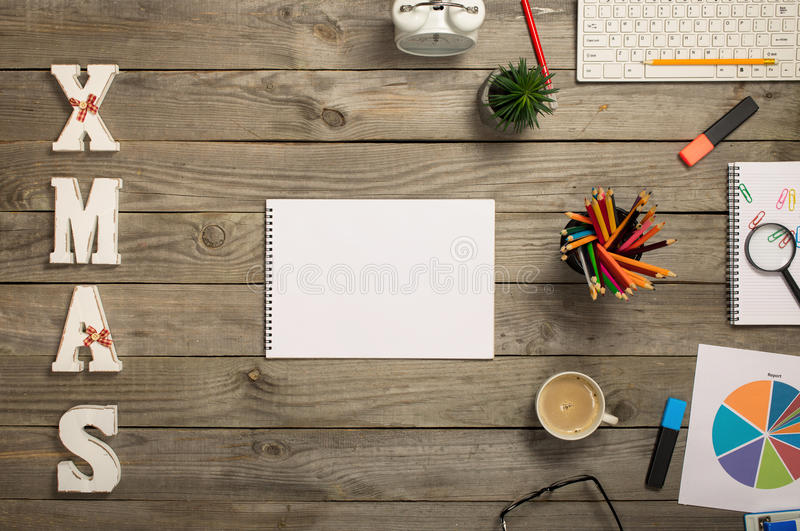 Open notebook with blank pages and various office items. Notepad with blank pages with cup of coffee, chart, keyboard, pencils, plant and word xmas on the wooden royalty free stock images