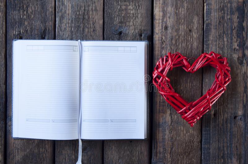 Open notebook with blank white pages. Wicker red heart for Valentine`s Day. On a wooden background. Open notebook with blank white pages. Wicker red heart for stock photography