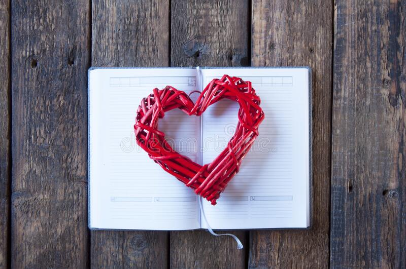 Open notebook with blank white pages. Wicker red heart for Valentine`s Day. On a wooden background. Open notebook with blank white pages. Wicker red heart for stock photos