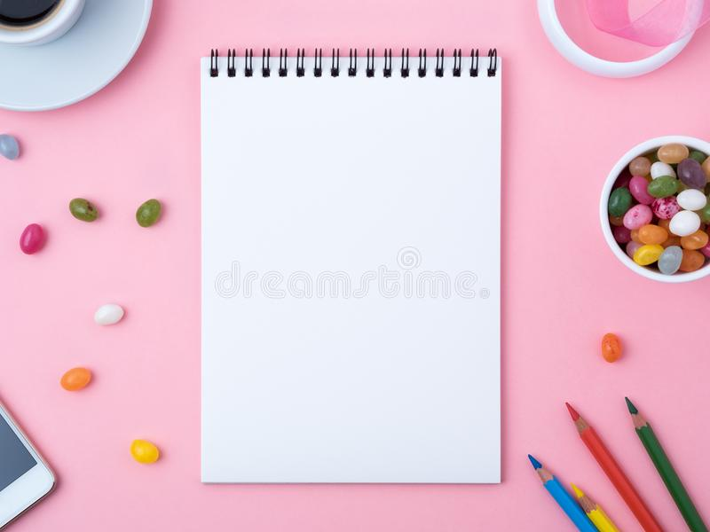 open notebook with a clean white sheet, caramel, lollipops, mobile phone, crayon, cup of coffee, decorations on a pink bright tab stock photos
