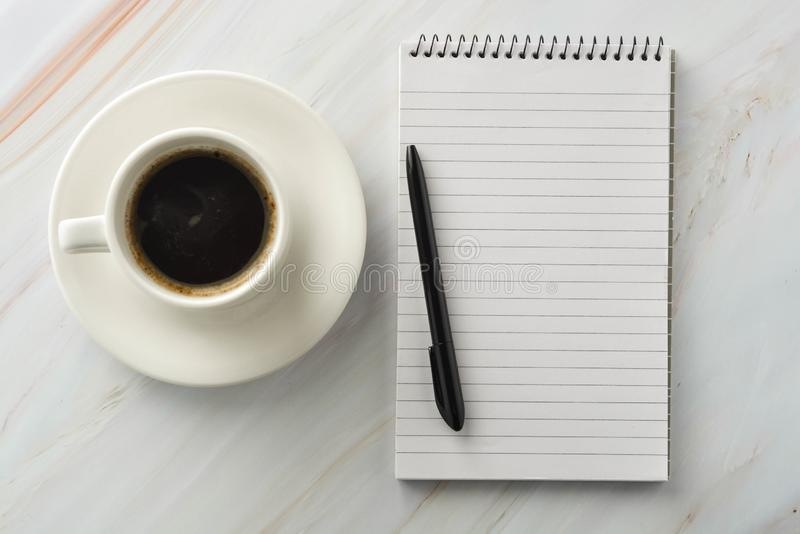 Open notebook with cup of coffee on marble desk. Workplace, work table. Top view. Open notebook with cup of coffee on marble desk. Workplace, work table royalty free stock images