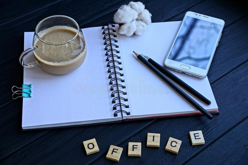 Open notebook with a cup of coffee pencils and a smartphone on the table and a word of wooden letters stock images