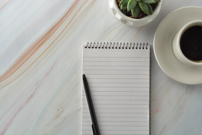 Open notebook with cup of coffee, succulent plant on marble desk. Workplace, work table. Top view. Open notebook with cup of coffee and succulent plant on marble royalty free stock photography