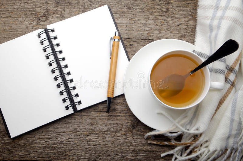 Open notebook and cup of tea stock images