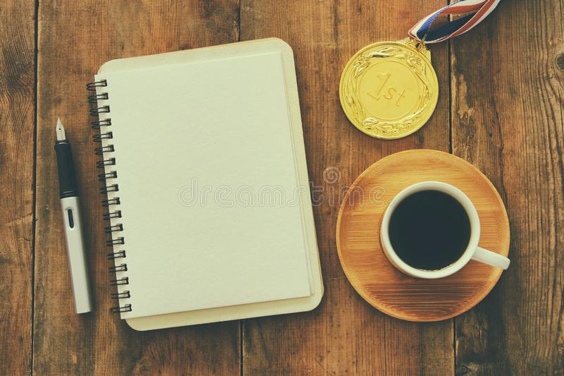Open notebook with empty pages and other office supplies over wooden old office desk table. Top view, flat lay royalty free stock images