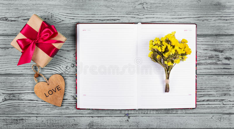 Open notebook, flowers and box with gift. Copy space. Wooden heart royalty free stock photos