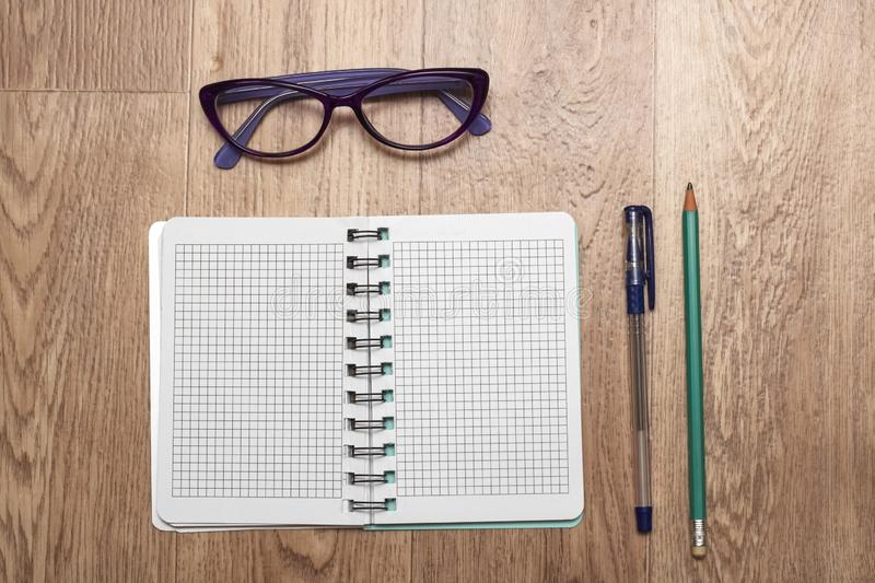 Open notebook, glasses, pen and pencil close up stock photography
