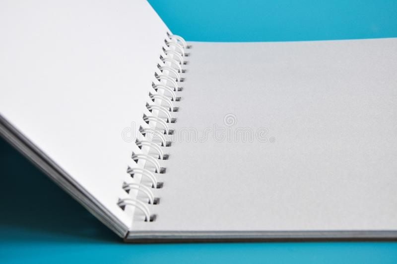 Open notebook. An open notebook isolated on a blue background royalty free stock image