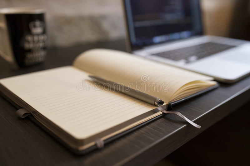 Open notebook and laptop stock photography