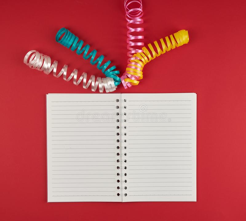 Open notebook in line and multicolored serpentine on a red background. Empty white sheets, top view stock images