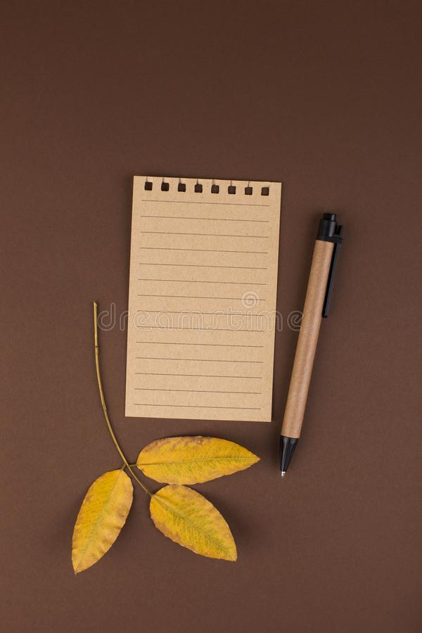 An open notebook for notes on a brown background. Office planning. Free space for text. Autumn atmosphere and yellow leaves. Top. View. Flay lay. Copy space royalty free stock photos