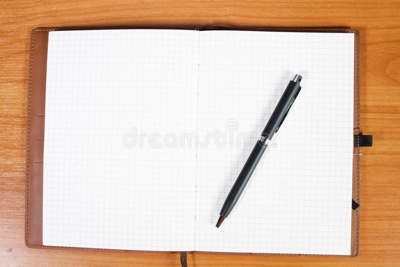 Open notebook with passport and pen over wooden. Background royalty free stock photo