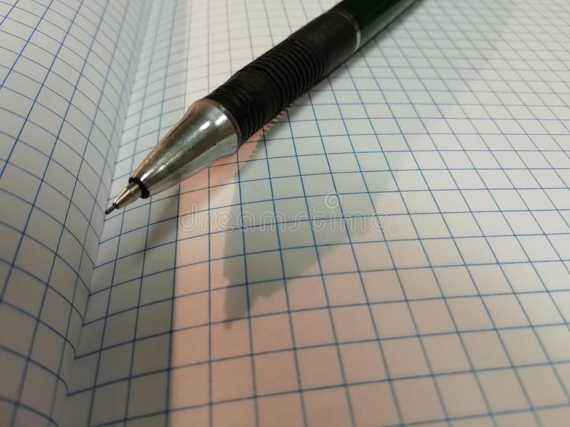Open notebook and pencil. Pencil shadow on notebook stock photo