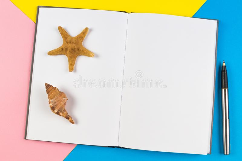 Open notebook with seashells and starfish on blue background. Vacation, travel concept royalty free stock images