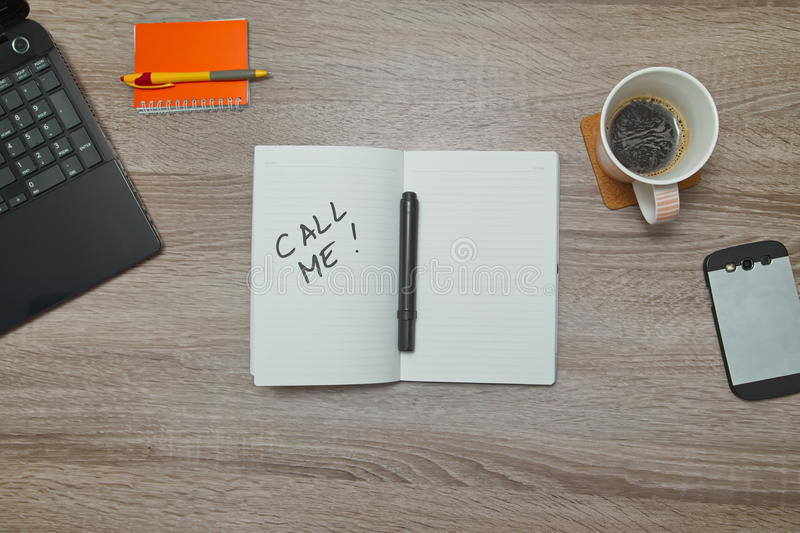 Open notebook with text `CALL ME` and a Cup of coffee on wooden background. Top down view royalty free stock photos