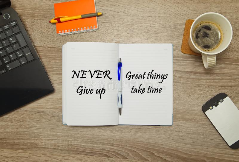 Open notebook with text `Never Give Up - great things take time` and a cup of coffee on wooden background. royalty free stock photos