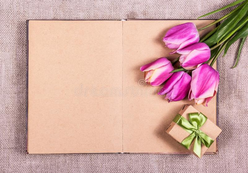 An open notebook, tulips and gift. Pink tulips and gift box. Copy space stock photos