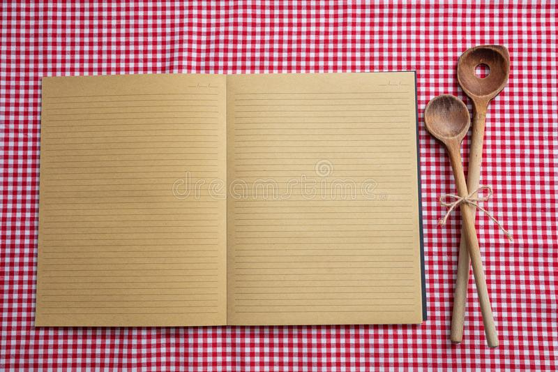 Open notebook, wooden kitchen utensils on red tablecloth, top view, copy space. Cooking recipe. Blank notebook and wooden kitchen utensils on red tablecloth, top stock images