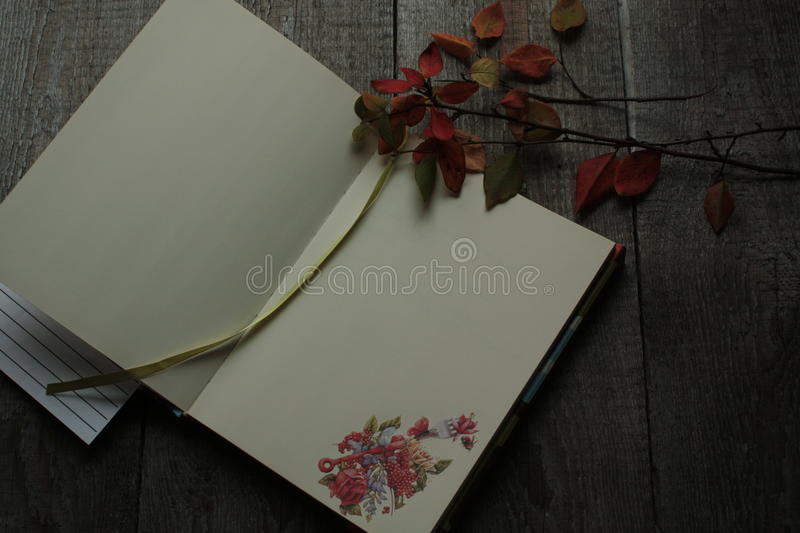 Open Notepad with autumn culinary sticker rests on a wooden stock photography