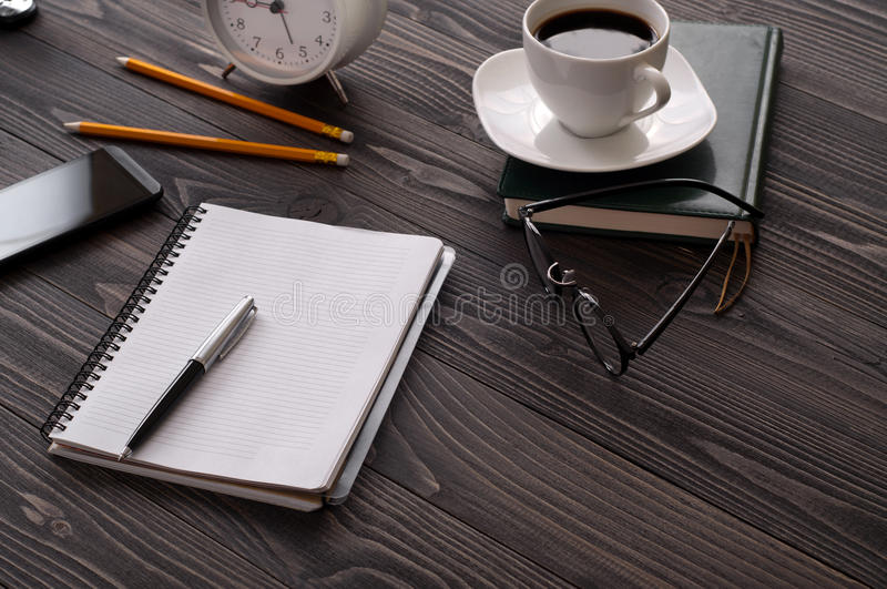 Open notepad with blank pages, a cup of coffee. And glasses on a wooden office desk. Top view with copy space stock images