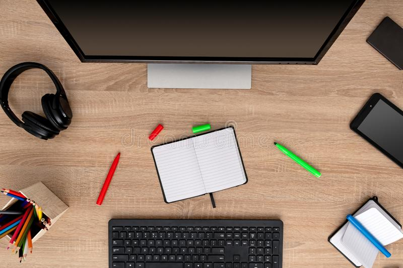 Open notepad with empty space for custom logo or text. Notebook, green marker, red marker, blue marker, pencils, display, keyboard and cell phone on wooden royalty free stock images