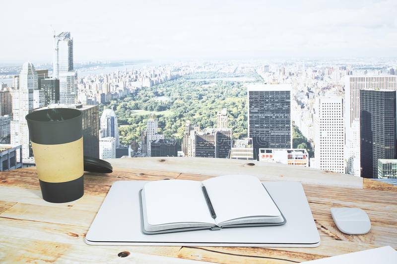 Open notepad on a wooden table with a a cup of coffee and a view. To Central Park of New York royalty free stock photos