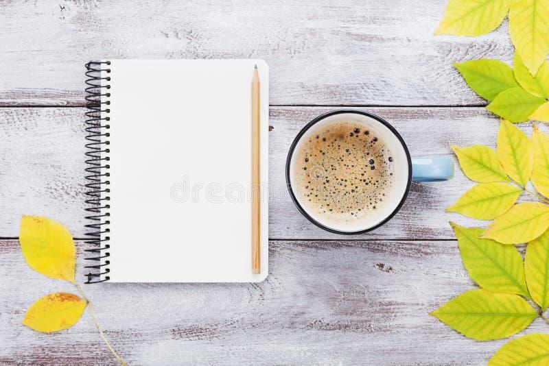 Open notitieboekje en ochtendkop van koffie op de rustieke houten mening van de lijstbovenkant De comfortabele van de de Dalingse stock foto's