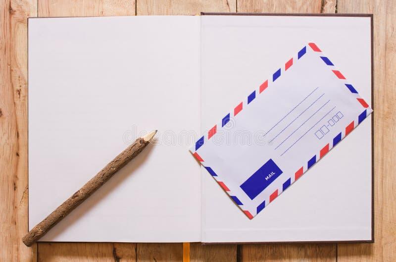 Open notitieboekje en post op houten achtergrond De ruimte van het exemplaar stock foto