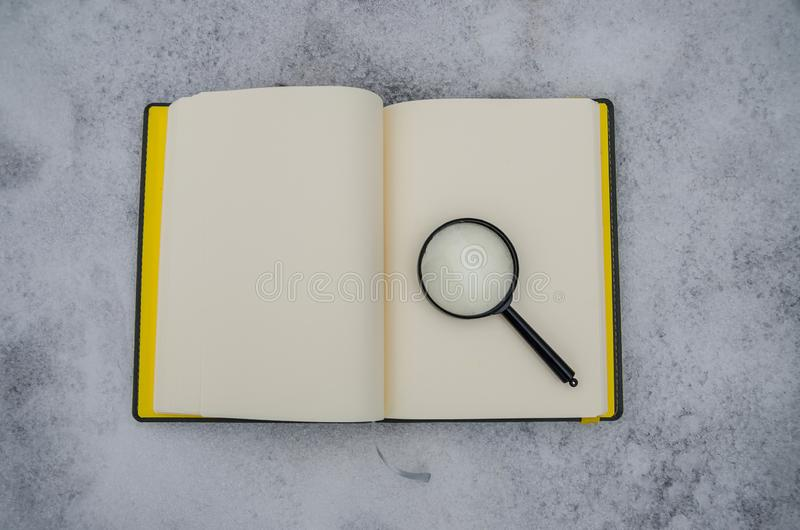 Open notitieboekje en vergrootglas op de achtergrond van witte sneeuw royalty-vrije stock fotografie