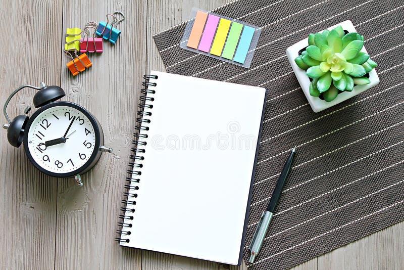 Open notitieboekje met blanco pagina's, en klok op houten bureaulijst royalty-vrije stock afbeeldingen