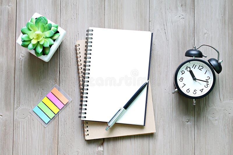Open notitieboekje met blanco pagina's, en klok op houten bureaulijst stock fotografie