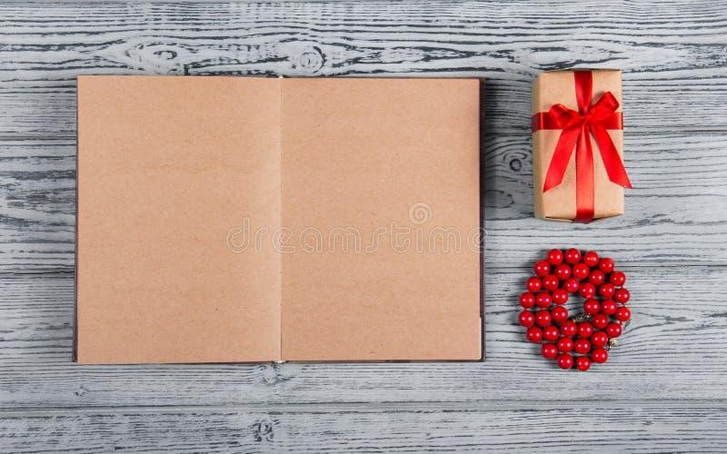 Open notitieboekje met blanco pagina's, rode koraalparels en weinig giftvakje met een boog Houten achtergrond Hoogste mening Vlak royalty-vrije stock foto's
