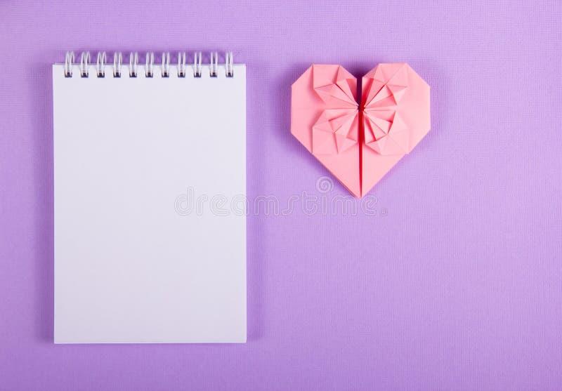 Open notitieboekje met een blanco pagina en een origamihart VALENTINE-DOCUMENT Roze document hart royalty-vrije stock fotografie