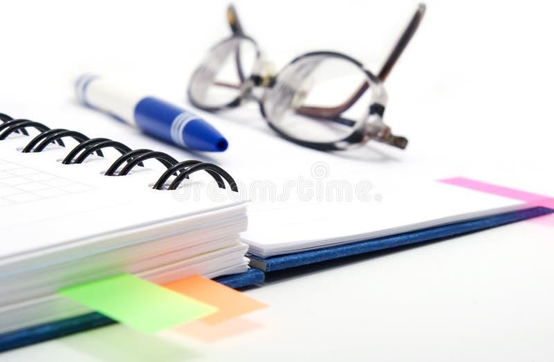 Open notitieboekje met glazen stock foto
