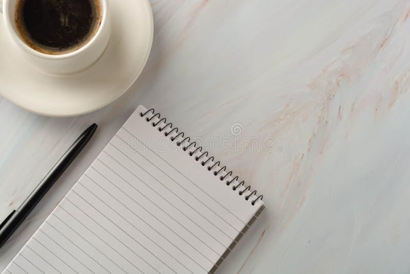 Open notitieboekje met kop van koffie op marmeren bureau Werkplaats, het werklijst Hoogste mening stock foto