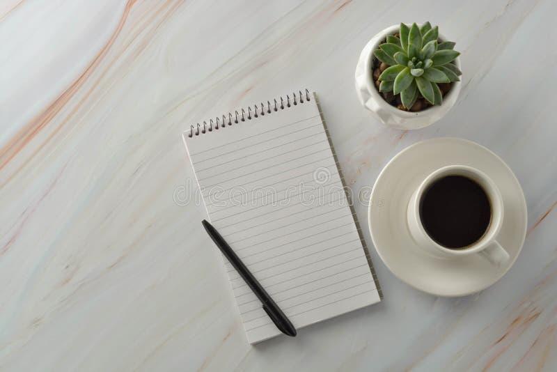 Open notitieboekje met kop van koffie, succulente installatie op marmeren bureau Werkplaats, het werklijst Hoogste mening stock afbeeldingen