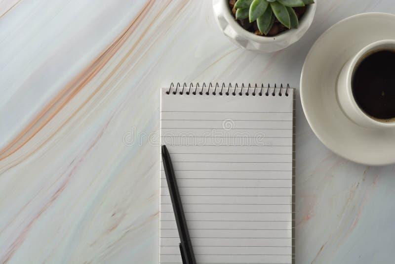 Open notitieboekje met kop van koffie, succulente installatie op marmeren bureau Werkplaats, het werklijst Hoogste mening royalty-vrije stock fotografie