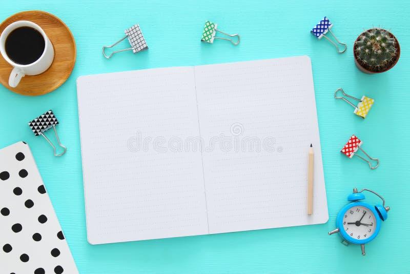 Open notitieboekje met lege pagina's en andere bureaulevering over lijst van het munt de blauwe bureau Hoogste mening stock foto