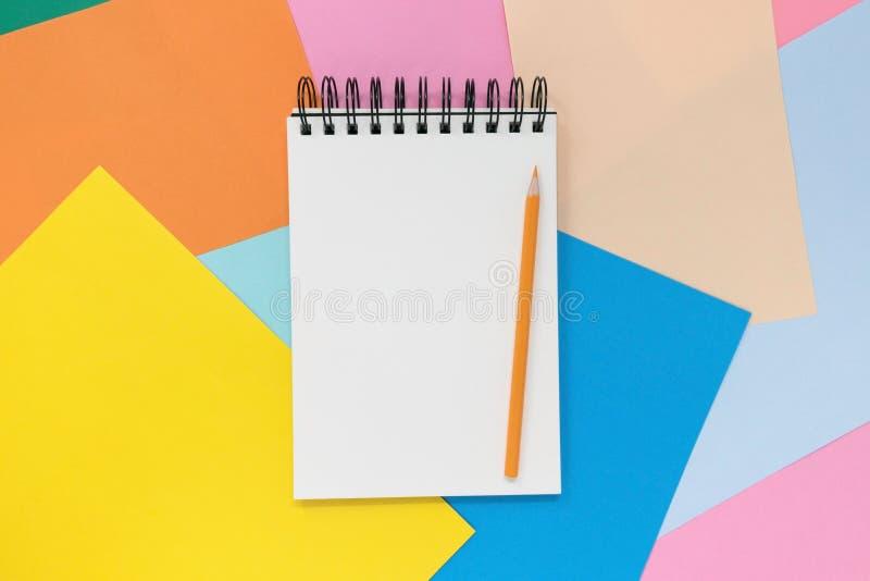 Open notitieboekje met oranje potlood op een multi gekleurde document achtergrond Hoogste mening met exemplaarruimte stock foto