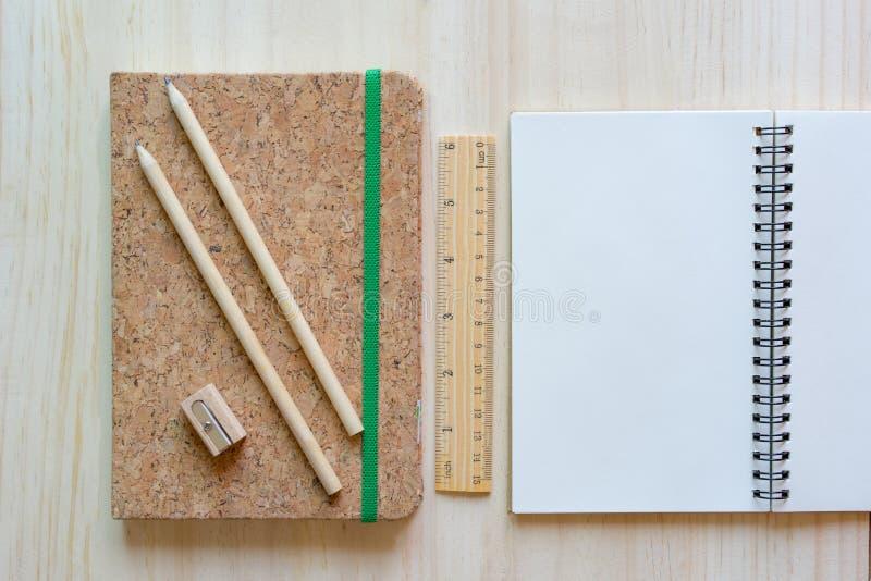 Open notitieboekje op houten achtergrond met potloden en heerser stock afbeeldingen