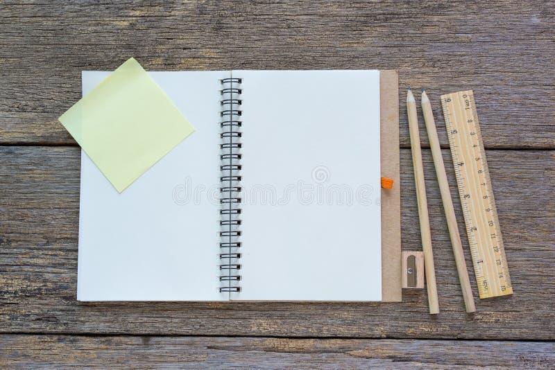 Open notitieboekje op houten achtergrond met potloden en heerser stock foto's