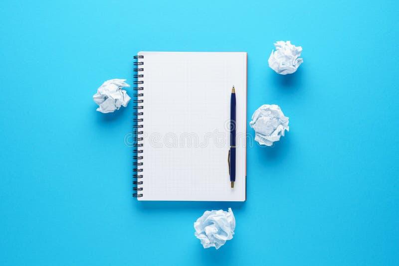 Open notitieboekje, pen en verfrommelde document ballen op blauwe achtergrond stock foto