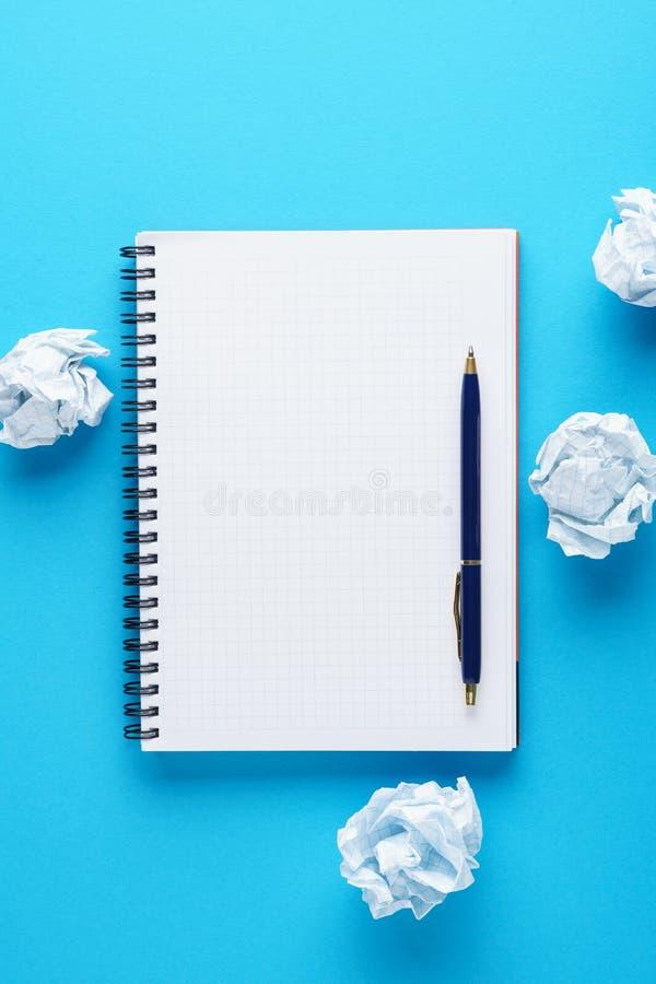 Open notitieboekje, pen en verfrommelde document ballen op blauwe achtergrond stock afbeeldingen