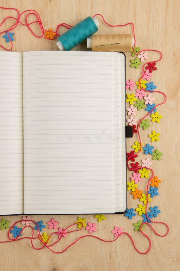Open notitieboekjepagina needlewoman met knopen, draad, bloemen en royalty-vrije stock afbeelding